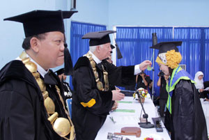 WISUDA: Rektor UMMI, Prof. Dr. Asmawi Zainul menyematkan tali toga saat wisuda UMMI yang ke-7 dan 8 di Aula UMMI, Jalan Syamsudin,kemarin. Foto:ikbal/radarsukabumi